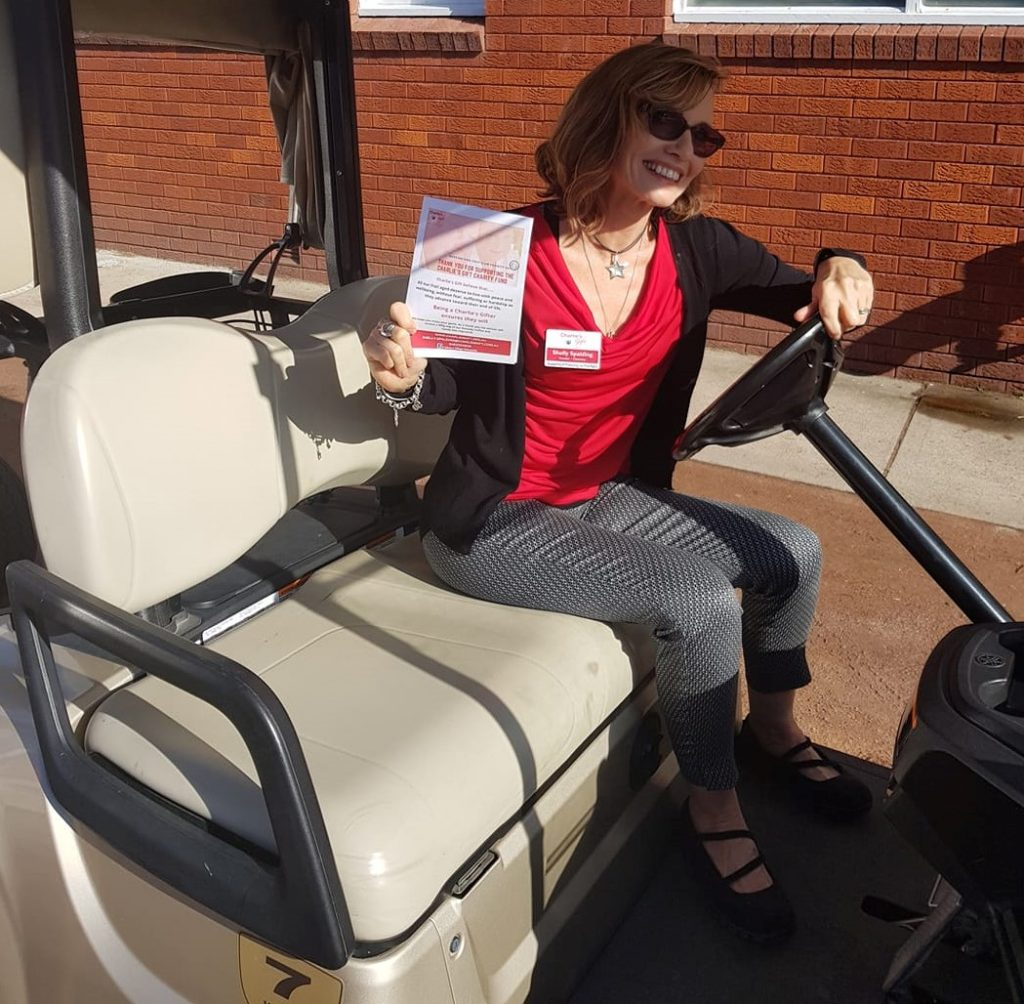Shelly driving golf cart at the charity golf day